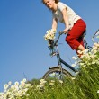 Woman with bicycle among spring flowers — Stock Photo #6410346