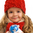 Little girl with a handful of snow and christmas bauble — Stock Photo #6411222