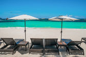 Beach umbrellas and loungers on perfect white beach — Stock Photo