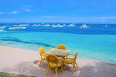 Table and chairs on tropical beach — Stock Photo