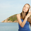 Foto Stock: Sea and Woman listening conch