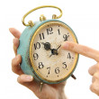 Old alarm clock in hands — Stock Photo #25235877