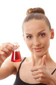 Woman in sports suit holds flask with red liquid — Stock Photo