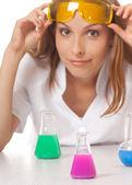 Kvinna kemist och kemikalier i kolvar — Stockfoto