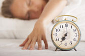 Young sleeping woman and alarm clock in bed — Stock Photo