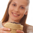 Woman holding a small bag of coffee beans — Stock Photo