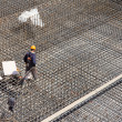 Stock Photo: Workers make reinforcement for concrete foundation