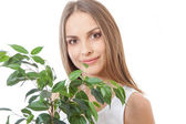 Female face behind grin foliage plant — Stock Photo