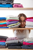 Young woman hiding behind a shelf with clothing — Photo