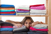 Young woman hiding behind a shelf with clothing — Stock Photo