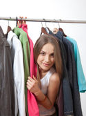 Young woman near rack with hangers — Stock Photo