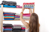 Young woman holding a pile of clothes — Stock Photo
