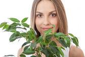 Kvinnliga ansikte bakom grin bladverk växt — Stockfoto