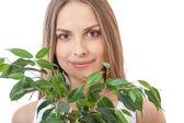 女性の顔をニヤリと笑う観葉植物の背後にあります。 — ストック写真