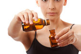Young woman holding two bottles of medicine — Stock Photo