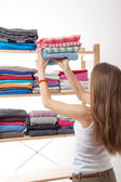 Young woman holding a pile of clothes — Stockfoto