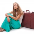 Girl sitting near a suitcase, isolated on white — Stock Photo