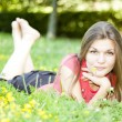 Beautiful girl lying in the grass in the park — Stock Photo #19736837