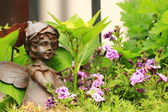 Flower-bed mit an angel statue — Stock Photo