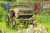 Vintage horse carriage in a flower bed — Stock Photo