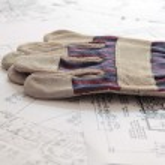 Gloves on blueprints — Stock Photo #18261661