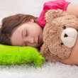 Stock Photo: Young girl taking a nap with her teddy bear