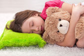 Young girl taking a nap with her teddy bear — Stock Photo