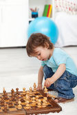 Toddler boy playing with chess pieces — Stock Photo