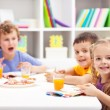 图库照片: Childhood friends eating together in kids room