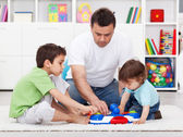 Father showing his sons a new toy — Stock Photo