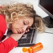 Exhausted woman asleep at work - Stock Photo