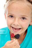 Little girl eating blackberries — Stock Photo