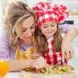 Woman and little girl making fresh fruits snack together - Stock Photo