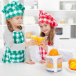 Little chefs making fresh orange juice in the kitchen — Stock Photo