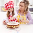 Little girl making her first fruit cake with some help — Stock Photo #13160011