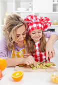 Woman and little girl making fresh fruits snack together — Stock Photo