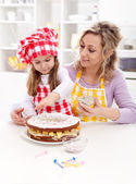 Little girl making her first fruit cake with some help — Stock Photo