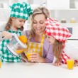 Stock Photo: Girls and their mother making fresh fruit juice