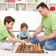 Boys playing chess with their father — Stock Photo