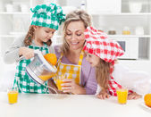Girls and their mother making fresh fruit juice — Stock Photo