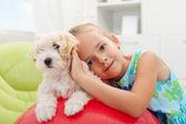 小さな女の子が彼女の小さなフワフワした犬と遊んで — ストック写真