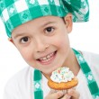 Child with chef hat holding muffin — Stock Photo