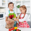 Kids unpacking the groceries - Stock Photo