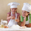 Kids with chef hats preparing the cake dough — Stock Photo #13844543