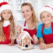 Family at christmas making a gingerbread cookie house — Stock Photo