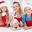 Family at christmas making a gingerbread cookie house — Stock Photo #14292923