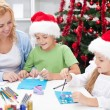 Family at christmas time making greeting cards — Stock Photo
