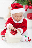 Baby girl in santa outfit opening a present — Stock Photo