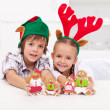 Happy christmas kids holding decorated gingerbread — Stock Photo #14719031