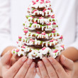 Stock Photo: Woman and child hands holding gingerbread decorated christmas tr